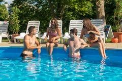 Fyra vänner som har gyckel i simbassängen Royaltyfri Bild