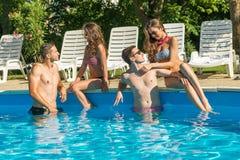 Fyra vänner som har gyckel i simbassängen Royaltyfri Fotografi
