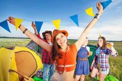 Fyra vänner som har gyckel utanför tält på campingplatsen royaltyfria foton