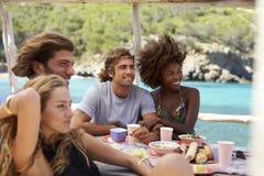 Fyra vänner som talar på en tabell vid havet, Ibiza, Spanien Arkivfoton
