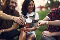 Fyra vänner som utomhus är och tillsammans sätter koppar kaffe fotografering för bildbyråer