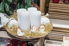 Fyra vita stearinljus på plattan med änglar Arkivbild