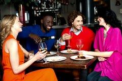 Fyra vänner som tycker om matställen på en restaurang Arkivbilder