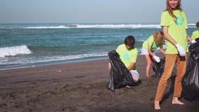 Fyra volontärer i gröna t-skjortor med bild återanvänder mot efterkrav avskräde på stranden som ser på kamera med påsar av samlat arkivfilmer