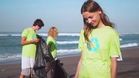 Fyra volontärer i gröna t-skjortor med bild återanvänder mot efterkrav avskräde på stranden som ser på kamera med påsar av samlat stock video