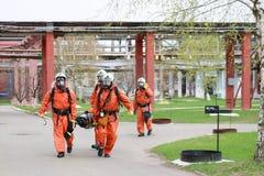 Fyra yrkesmässiga brandmanbrandmän i orange skyddande brandsäkra dräkter, vita hjälmar och gasmaskar bär det sårat per royaltyfria bilder
