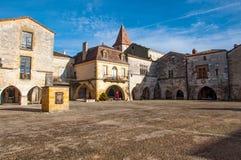 Fyrkant och farstubro byn av Monpazier royaltyfri bild