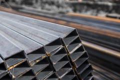 Fyrkanten lägenhet-rullade rörmetallprofil i packar på lagret av metallprodukter Red ut metallprofiler för royaltyfri foto