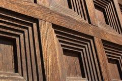 Fyrkanter mönstrar på den gamla trädörren, closeupbild Arkivbild