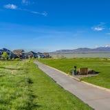 Fyrkantig bana under ett rikt grönt fält som leder till hus i avståndet arkivfoto