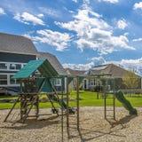 Fyrkantig lekplats för ram på ett rikt grönt fält som omges av träd och hus royaltyfria foton