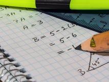 Fyrkantig matematikstudentbok och färgad blyertspenna på den royaltyfri bild