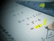 Fyrkantig matematikstudentbok och färgad blyertspenna på den arkivfoto