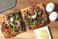 Fyrkantig pizza på den wood tabellen Arkivbild