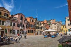 Fyrkantig sikt av färgrika gamla byggnader, restauranger och folk i Venedig Arkivbilder