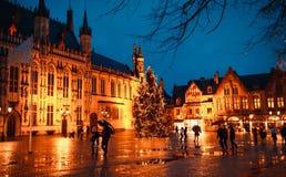 Fyrkantig småstad i Bruges på natten med det dekorerade päls-trädet för ` s för nytt år Royaltyfri Fotografi
