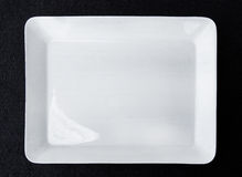 Fyrkantig vit platta som isoleras på svart bakgrund Royaltyfri Bild