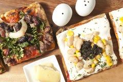 Fyrkantiga pizzaskivor på brädet Fotografering för Bildbyråer