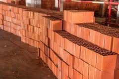 Fyrkantiga röda tegelstenar som staplas på en konstruktionsplats Royaltyfri Foto