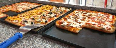 Fyrkantiga stycken av pizza. Fotografering för Bildbyråer
