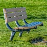 Fyrkantigt slut för ramram upp av en tom bänk mot ett rikt grönt gräs- fält på en solig dag arkivfoton