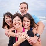 Fyrkantigt slut upp av den lyckliga familjen som ler all in mot kamera Royaltyfri Bild
