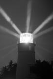 Fyrstrålar från Lens regniga nattpelare av ljus Royaltyfri Foto