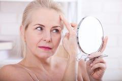 Fyrtio år gammal kvinna som ser skrynklor i spegel Plastikkirurgi- och collageninjektioner makeup Makroframsida Selektivt fokuser royaltyfri bild