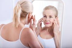 Fyrtio år gammal kvinna som ser skrynklor i spegel Plastikkirurgi- och collageninjektioner makeup Makroframsida Selektivt fokuser royaltyfria bilder