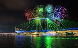 Fyrverkeri över den Singapore staden på natten med laser-show i marina Royaltyfria Bilder