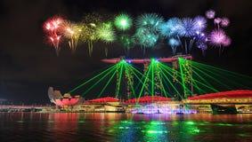 Fyrverkeri över den Singapore staden på natten med laser-show i marina Royaltyfri Bild