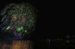 Fyrverkerier över havet i storstaden, konturer av folk Royaltyfri Foto