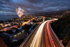 Fyrverkerier över ljusa slingor av bilar på tamarinvägen i Saint Paul, Reunion Island royaltyfri fotografi