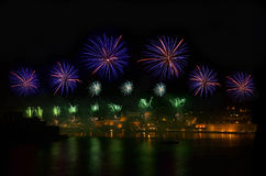 Fyrverkerier Fyrverkeriexplosionen i mörk himmel med stadssillouthe och färgrikt reflekterar på vatten i Valletta, Malta violetta Arkivfoto