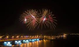 Fyrverkerier över staden i den stora floden med bron i ljus Arkivfoto
