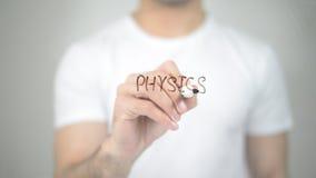 Fysica, mens die op het transparante scherm schrijven Stock Fotografie