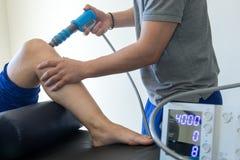 Fysieke therapie van de knie en de voet met drukgolf stock foto
