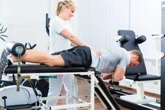 Fysioterapeut eller sportdoktor med patienten Arkivfoto