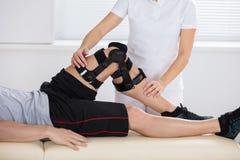 Fysioterapeut Giving Leg Exercise arkivfoto