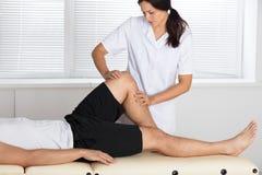 Fysioterapeut Giving Leg Exercise i klinik fotografering för bildbyråer
