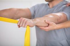 Fysioterapeut Giving Man en utbildning med övningsmusikbandet royaltyfria foton