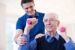 Fysioterapeut Helping Senior Man som lyfter handvikter Royaltyfri Foto