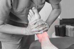 Fysioterapeut kiropraktor som gör en fotmassage till manpatienten osteopathy arkivbild