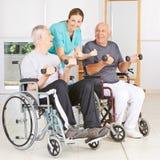 Fysioterapeut med två höga män i rullstolar Arkivfoto