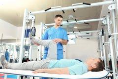Fysioterapeut som arbetar med patienten arkivbild