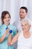 Fysioterapeut som försäkrar pensionären under övning Arkivbilder