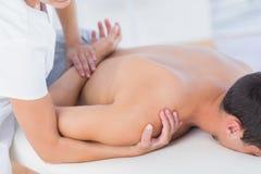 Fysioterapeut som gör skuldramassage till hennes patient arkivfoton