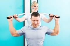 Fysioterapeut som gör sportrehabilitering med patienten Arkivbild