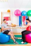 Fysioterapeut som ger patienter gymnastisk övning Royaltyfri Foto