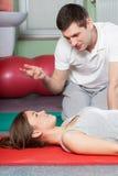 Fysioterapeut som ger rådgivning till den kvinnliga patienten Arkivbilder